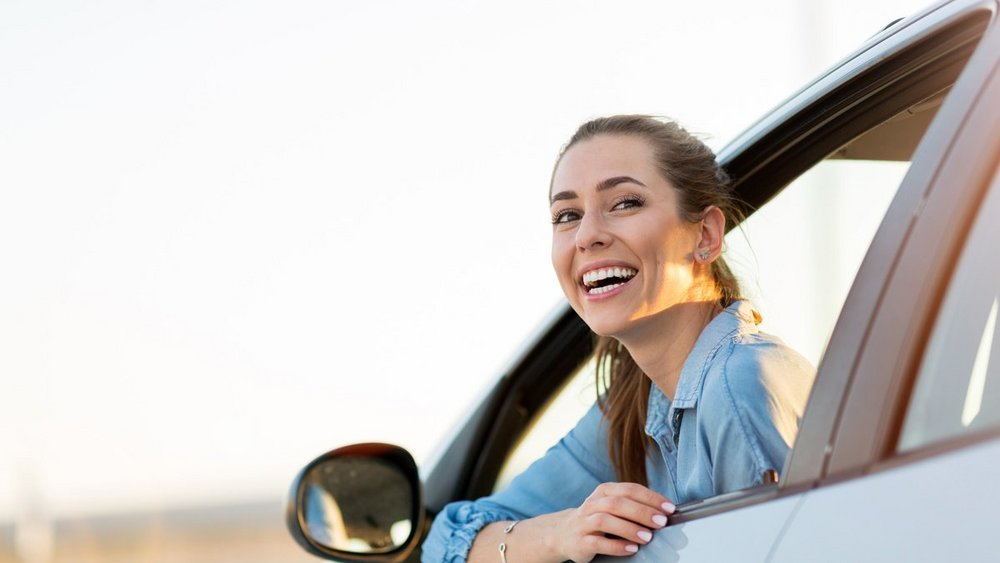 A Woman smiles out of the drivers door windows of her car.